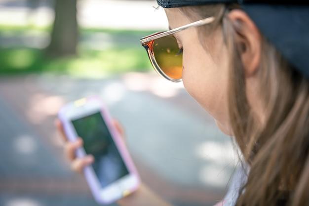 Il focus è sugli occhiali da sole sul viso della ragazza che guarda il telefono.