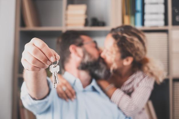 Focus sulle chiavi, detenute da entusiasti giovani sposi proprietari di case. felice coppia di famiglia sposata che celebra il trasloco in una nuova casa, dimostrando le chiavi, in piedi in appartamento, concetto di mutuo immobiliare.