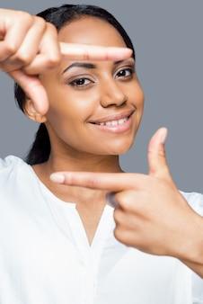 Concentrati su di me! ritratto di giovane donna africana giocosa che gesticola la cornice del dito e lo guarda con un sorriso mentre si trova su uno sfondo grigio