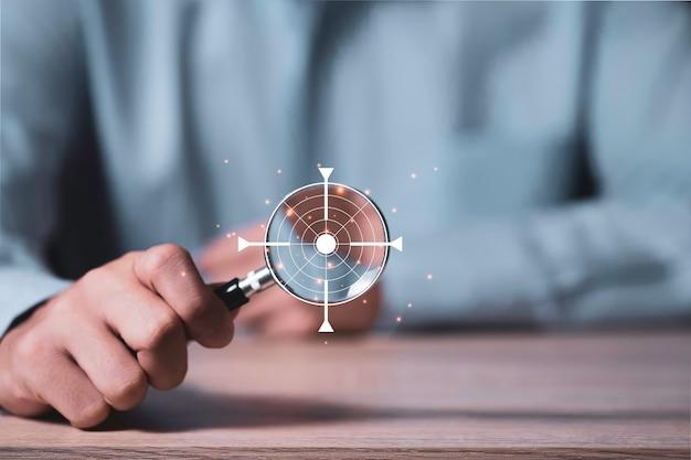 Concentrarsi nel concetto di obiettivo e obiettivo obiettivo, manager dell'uomo d'affari che tiene il vetro della lente d'ingrandimento con la scheda obiettivo virtuale sulla tavola di legno con lo spazio della copia.