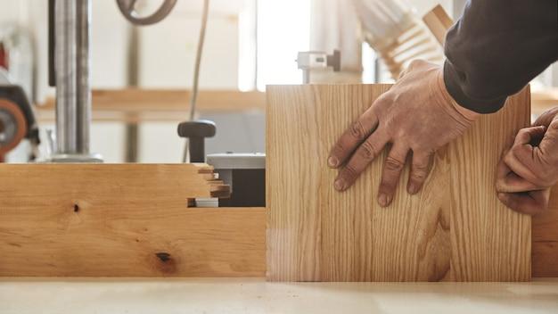 Concentrati sul falegname di qualità che lavora con uno strumento industriale nella fabbrica di legno