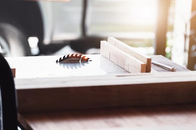 Focus sulla lama per il taglio del legno tronchi che stanno per essere tagliati sul banco da lavoro. per la lavorazione del legno come ordinato dal cliente