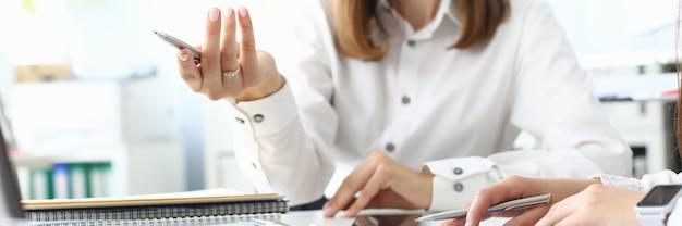 Concentrarsi su smart imprenditrice seduti al chiuso e tenendo la penna di scrittura metallica. responsabile femminile spiritoso che discute qualcosa di importante con il collega. contabilità concetto di ufficio. sfondo sfocato