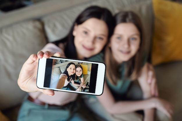 Concentrarsi sullo schermo dello smartphone con selfie di madre e figlia, stretta relazione tra il concetto di madre e figlia