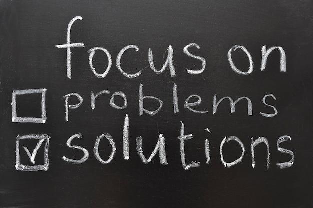 Concentrarsi sulle soluzioni, citazione motivazionale sulla lavagna