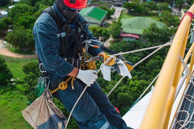 Messa a fuoco vista dall'alto lavoratore di sesso maschile in basso altezza serbatoio tetto accesso fune ispezione di sicurezza dello spessore del serbatoio di stoccaggio gas propano.