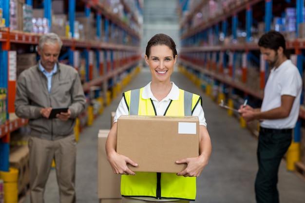 Focus sul lavoratore è in possesso di scatola di cartone e sorridente