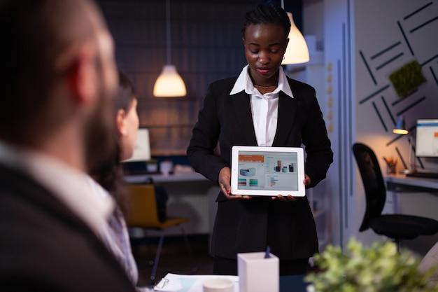 Donna d'affari afroamericana focalizzata che mostra grafici aziendali su tablet che lavora nella sala riunioni dell'ufficio a tarda notte. diverse idee di strategia aziendale di brainstorming di lavoro di squadra multietnico