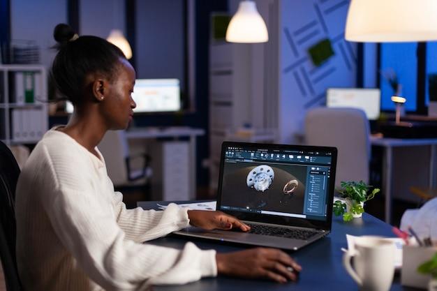 Donna ingegnere afroamericana focalizzata che lavora al prototipo di ingranaggio industriale