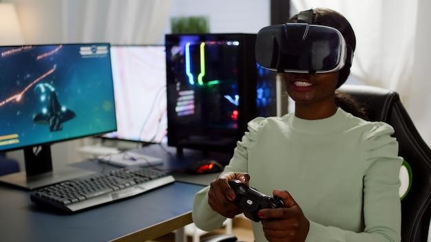 Giocatore cibernetico africano concentrato che indossa cuffie per realtà virtuale durante il campionato online che tiene il controller