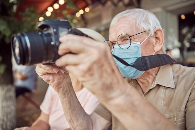 Uomo caucasico invecchiato concentrato in occhiali e una maschera facciale che fotografa con la sua fotocamera digitale