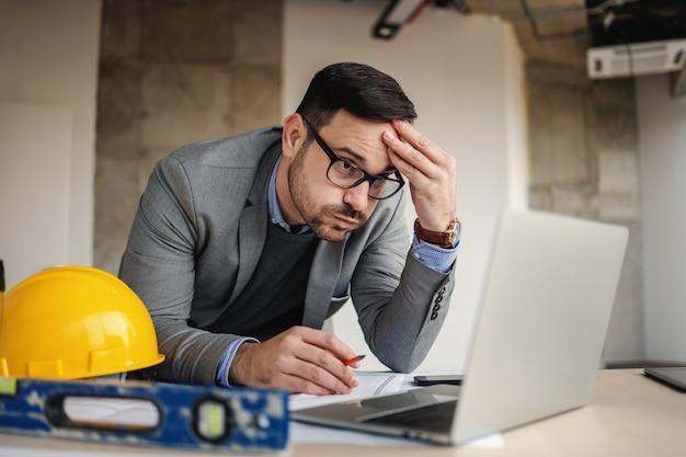 Architetto concentrato che tiene la sua testa, punti panoramici e guardando il laptop.