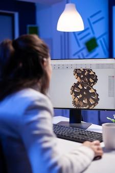 Architetto concentrato che lavora a un nuovo progetto utilizzando il computer facendo prototipi di ingranaggi a tarda notte seduto alla scrivania nell'ufficio di avvio