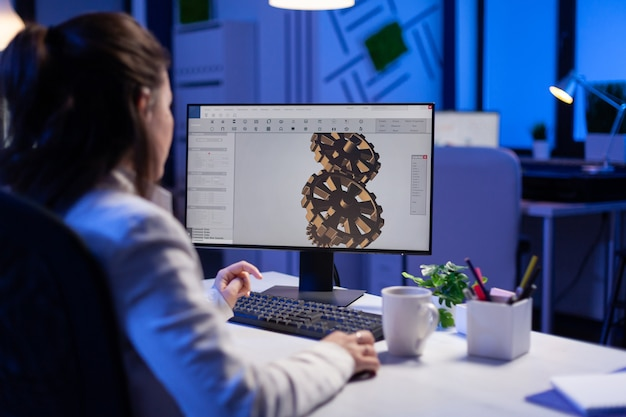 Architetto concentrato che lavora a un nuovo progetto utilizzando il computer facendo il prototipo dell'ingranaggio a tarda notte