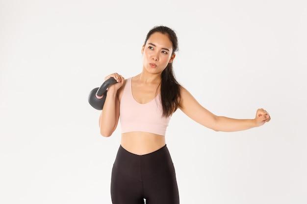 Concentrato asiatico forte gitl solleva il peso in palestra, allenamento da casa con kettlebell, controllo della respirazione durante esercizi di fitness, sfondo bianco.