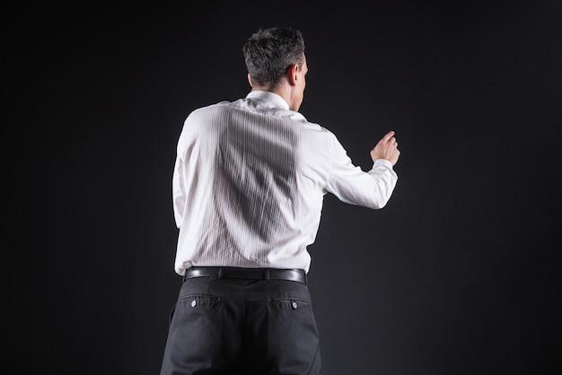 Attenzione focalizzata. uomo serio bello bello in piedi davanti allo schermo sensoriale e premendolo mentre si concentra sul suo lavoro