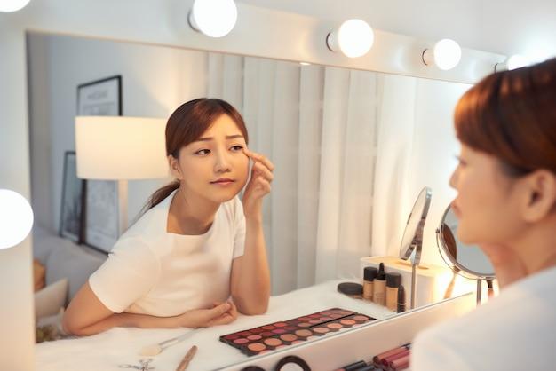 Bella giovane donna asiatica concentrata che si guarda allo specchio