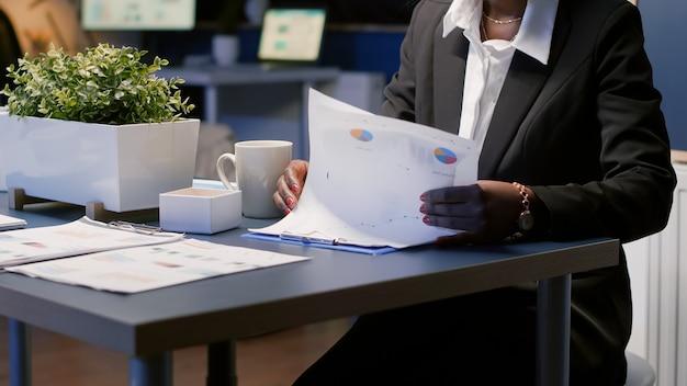 Donna d'affari afroamericana nera concentrata che fa gli straordinari alla presentazione della gestione aziendale a tarda notte nella sala riunioni dell'ufficio. direttore esecutivo che analizza i documenti di profitto finanziario