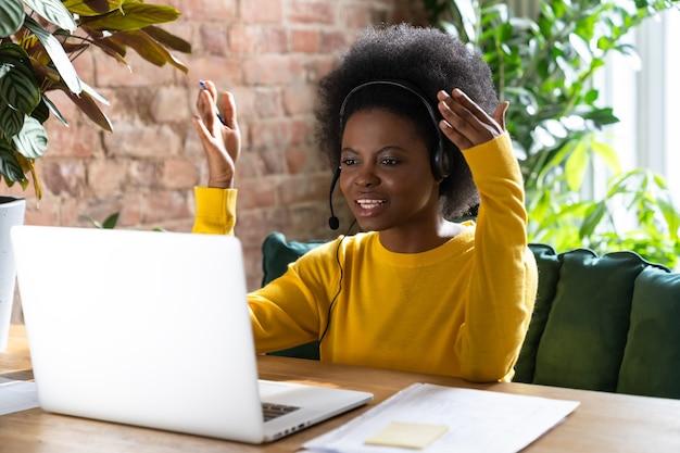 Concentrato donna nera dipendente che indossa le cuffie, parlando in videochiamata con i clienti sul laptop