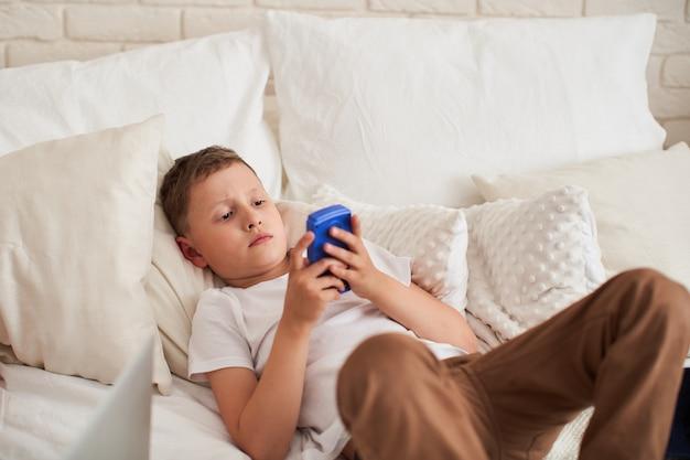 Il ragazzo concentrato è steso su un letto e sta giocando a un videogioco.