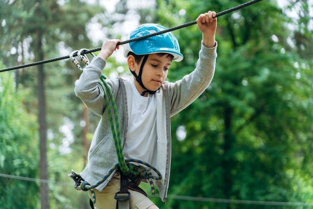 Un ragazzo concentrato con un casco protettivo gestisce una funivia in un parco di funi. il bambino trascorre attivamente il tempo