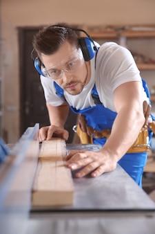 Falegname concentrato che controlla il legname sulla sega da tavolo