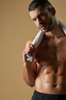 Atleta caucasico concentrato con un corpo muscoloso che mostra il suo corpo atletico con il torso nudo nel