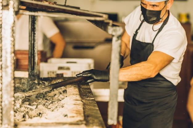 Chef concentrato che indossa maschera facciale e retina per capelli che cucina carne alla griglia e lavora al ristorante.
