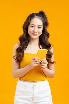 Messaggio di sms di donna riccia focalizzata. studio shot di elegante ragazza con smartphone su sfondo giallo.