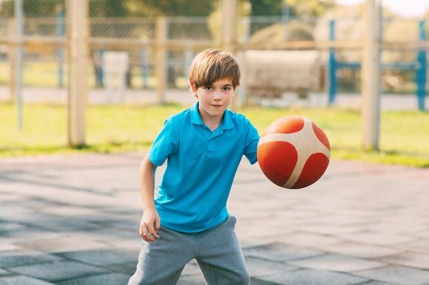 Focalizzato atleta ragazzo carino conduce la palla in una partita di basket. un ragazzo gioca a basket dopo la scuola