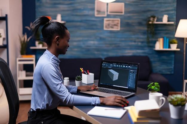Donna dalla pelle scura concentrata che lavora alla scadenza del progetto ingegnere femminile nero industriale che studia l'idea del prototipo sul personal computer che mostra il software sul display del dispositivo