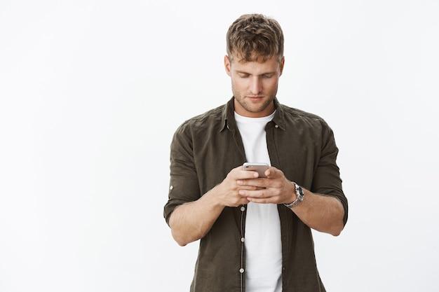 Ragazzo europeo biondo concentrato e determinato che tiene in mano uno smartphone che guarda concentrato sullo schermo del telefono cellulare mentre gioca a un'app o fa scorrere il feed di notizie nel social network sul muro grigio