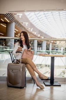 Donna elegante focalizzata che chiacchiera navigando in internet con un bicchiere di carta da caffè nell'area duty free della lounge