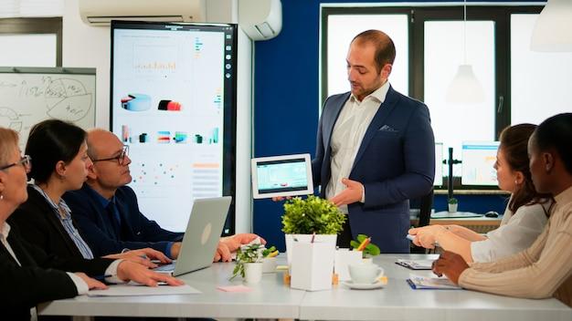 Manager esecutivo focalizzato che presenta relazione finanziaria annuale tenendo tablet in piedi al tavolo della conferenza di fronte a diversi uomini d'affari. team multietnico che lavora in una startup