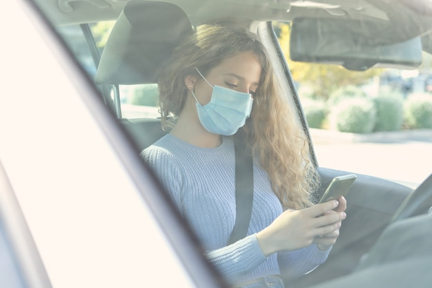 Autista femminile focalizzata in maschera che naviga su smartphone in auto