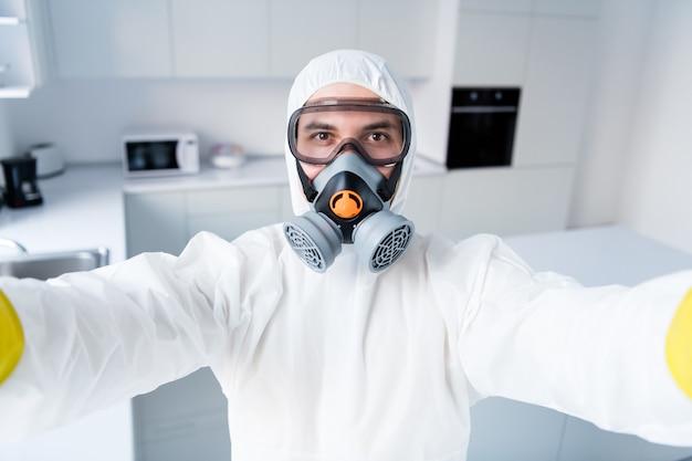Concentrato ragazzo lavoratore pulitore blogger in tuta fare selfie