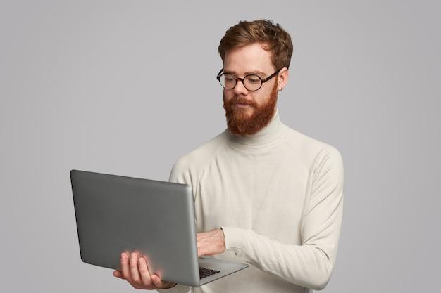Uomo bello messo a fuoco che per mezzo del computer portatile