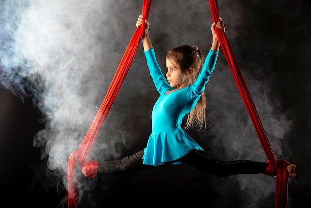 Focalizzato bambina graziosa in una tuta da ginnastica blu fa una spaccata in aria aggrappandosi a nastri rossi ariosi circondati da fumo su un nero