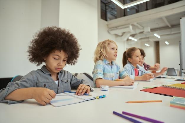 Piccolo scolaro concentrato che legge le note durante la lezione diversi bambini che studiano seduti insieme al