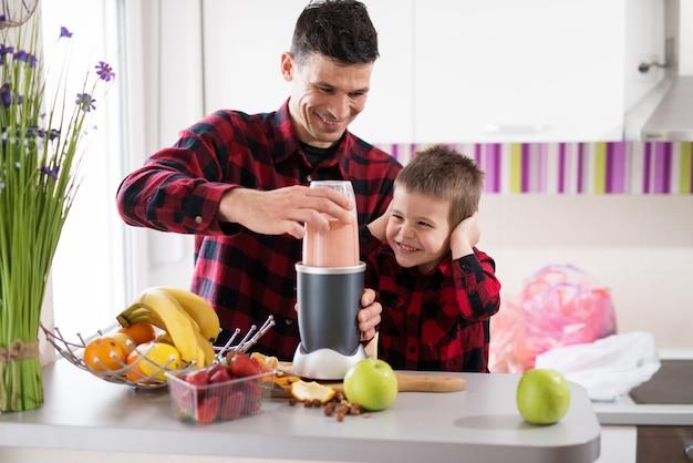 Il padre amorevole concentrato sta usando il frullatore per preparare il frullato mentre suo figlio tiene le orecchie mentre sorride in una cucina luminosa.