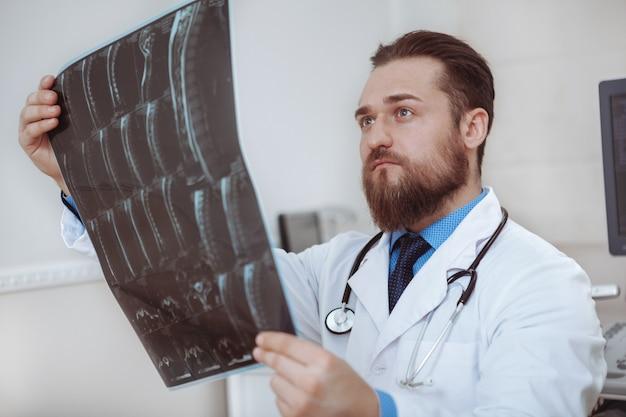 Lavoratore medico maschio messo a fuoco che esamina le esplorazioni di mri di un paziente
