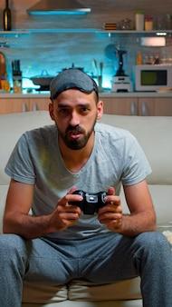 Uomo concentrato che tiene il joystick mentre è seduto davanti alla televisione