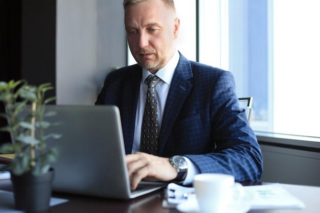 Concentrato uomo d'affari maturo immerso nei suoi pensieri mentre è seduto a un tavolo in un ufficio moderno.