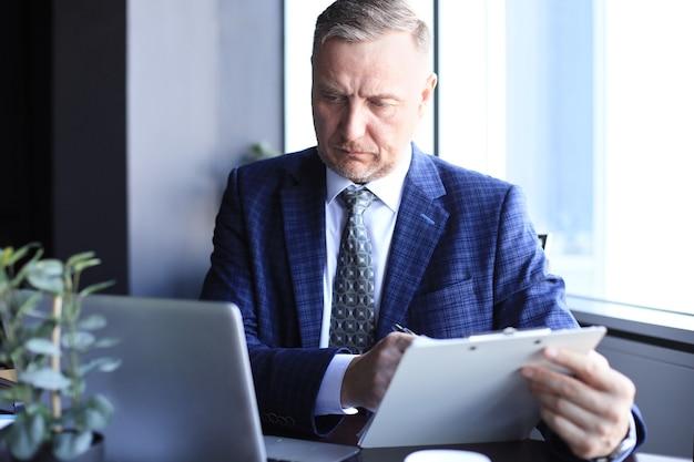 Concentrato uomo d'affari maturo immerso nei suoi pensieri mentre è seduto a un tavolo in un ufficio moderno. Foto Premium