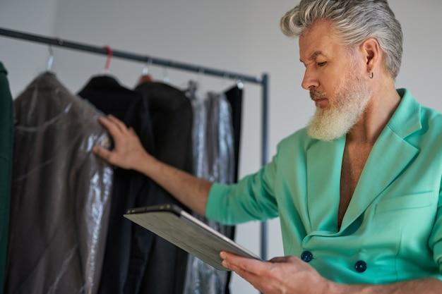 Uomo maturo concentrato, stilista professionista che indossa abiti colorati utilizzando tablet pc mentre è seduto accanto a un appendiabiti e controlla la disponibilità di articoli in studio. servizio fotografico di moda, concetto di stile