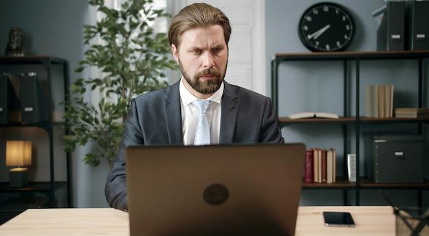 Uomo d'affari di mezza età messo a fuoco in vestito convenzionale che lavora al computer portatile che si siede alla scrivania