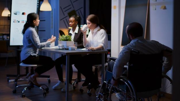 Uomo d'affari handicappato oberato di lavoro concentrato in sedia a rotelle che condivide statistiche di scartoffie finanziarie superlavoro nella sala riunioni dell'ufficio d'affari. diverse idee aziendali di brainstorming multietnico in serata