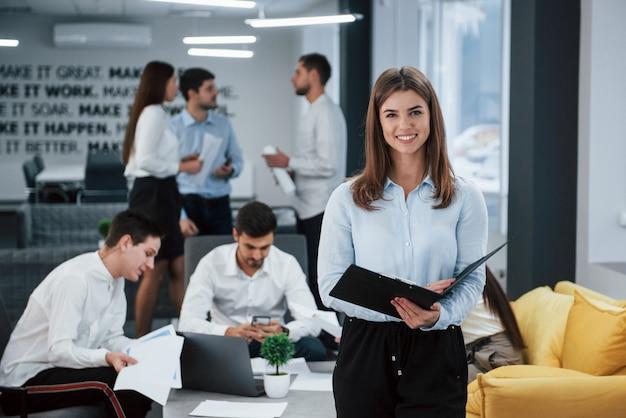 Foto focalizzata. il ritratto della ragazza sta nell'ufficio con gli impiegati a fondo
