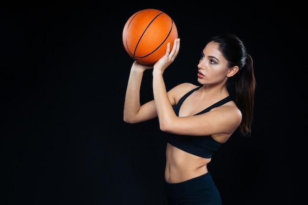 Concentrato piuttosto giovane atleta donna in piedi e lanciando palla da basket su sfondo nero black