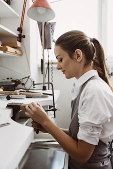 Incentrato su un processo. vista laterale del giovane gioielliere femminile che realizza un nuovo prodotto nel suo laboratorio di gioielleria. processo di creazione di gioielli. affare. laboratorio di gioielli.